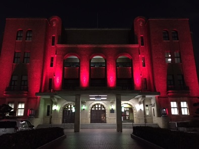 赤色にライトアップされた公会堂外観の写真