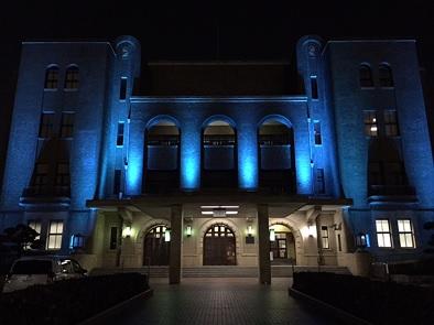 青色にライトアップされた公会堂外観の写真