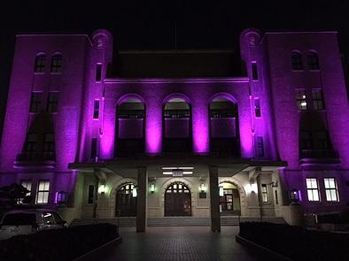 紫色にライトアップされた公会堂外観の写真
